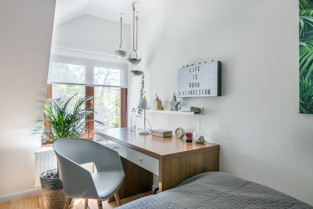 Szobabelső barna íróasztallal, szürke székkel és ággyal, szövegdobozzal a falon. Tetőtér.