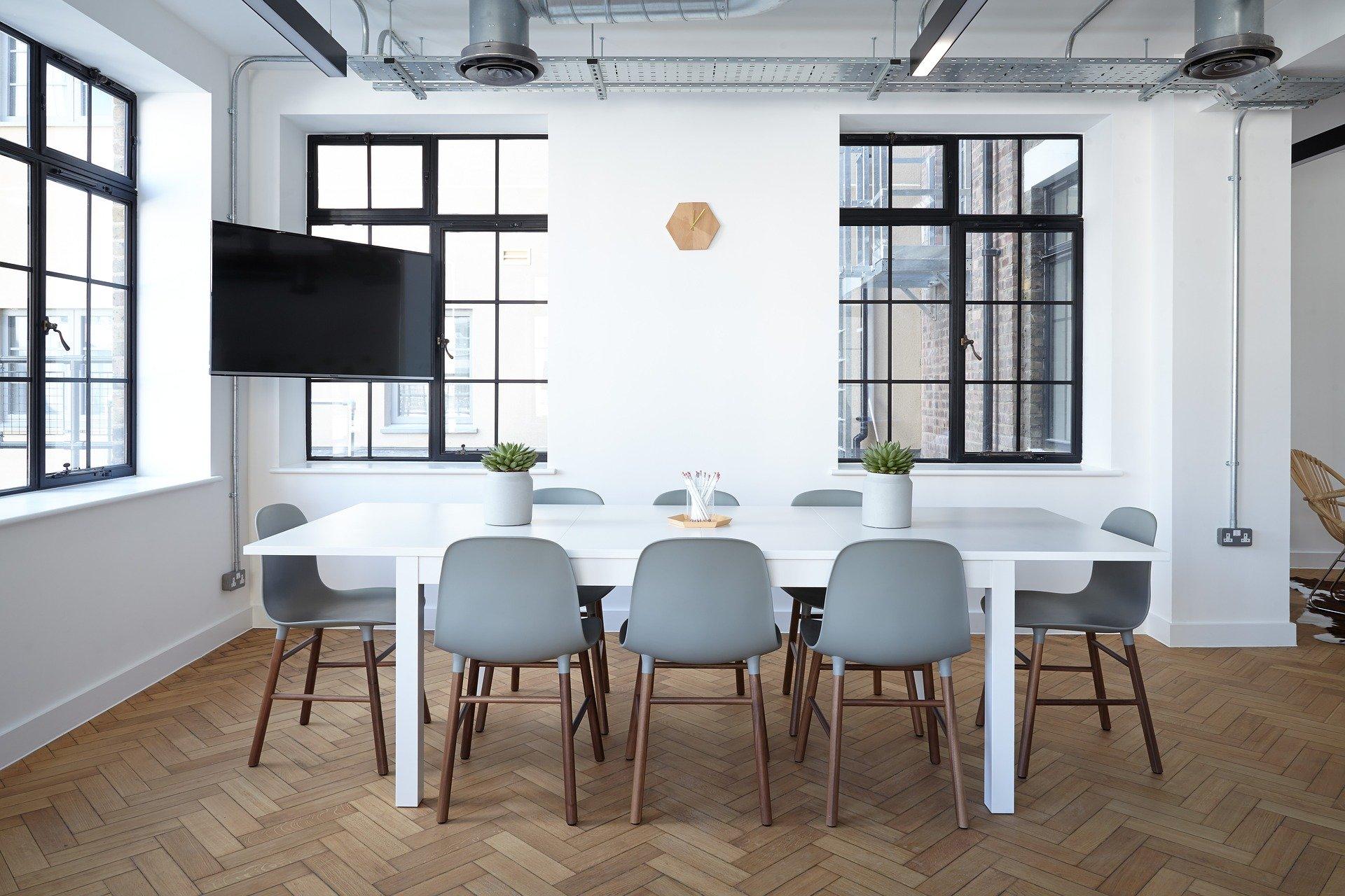 tárgyaló szürke székekkel fehér asztallal fekete ablakkeretekkel