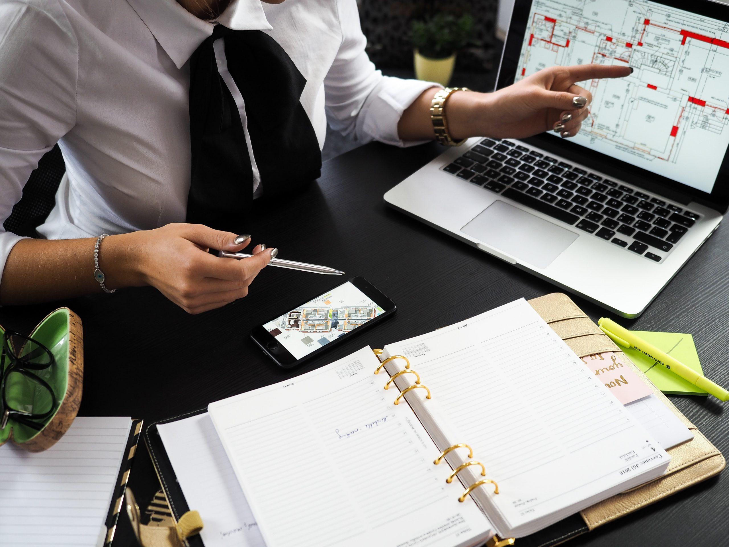 tervezőasztalon füzetek, számítógép, női kezek magyarázón